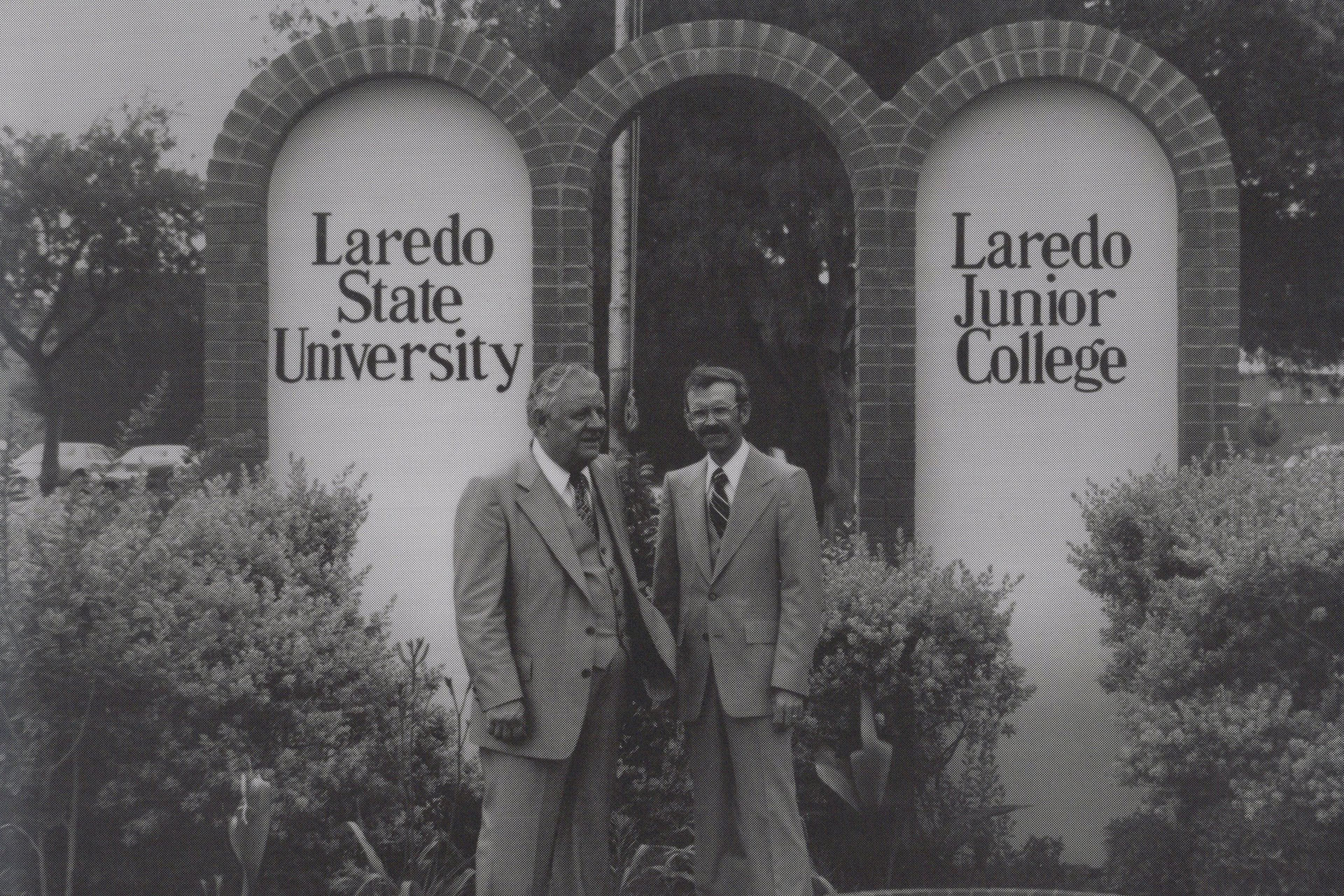 Two men standing in front of a mural that reads 'Laredo State College' and 'Laredo Junior College'.