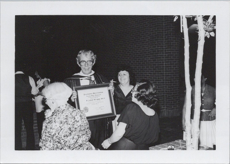 A smiling Dr. Briggs holds a certificate to the camera while being surrounds by friends.
