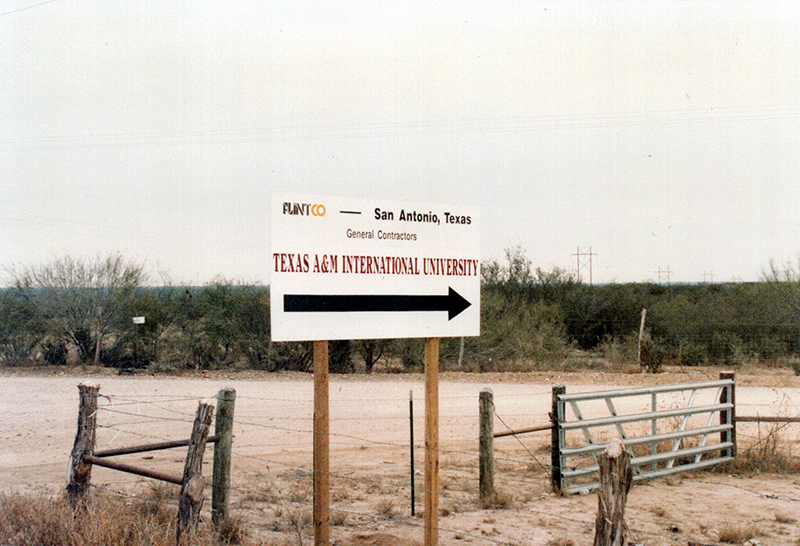 a plain white Contruction sign that reads 'Texas A&M International University' with a black arrow point to the right. Behind the sign is cleared out land.
