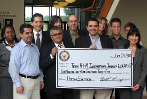 Congressman Henry Cuellar holding $6M check.