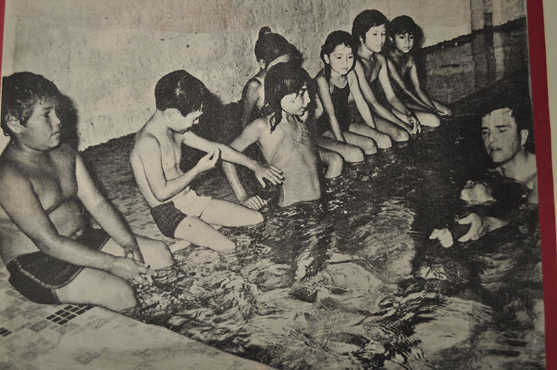 In a community pool, Dr. Ball teaches a young boy how to perfect his back stroke. Seven young children are sitting attentively on the pool's edge.
