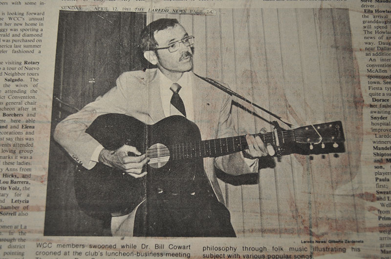 Dr. Billy Cowart plays his acoustic guitar in a light suit.
