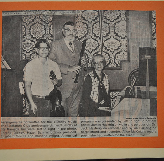 A young boy with oversized glasses and medium width hair that is parted down the middle is holding a violin. Next to him are his parents. His father, who sports a grand beard, holds a recorder while his mother, a woman with short hair fashioned into a bob cut, is seated at a piano.
