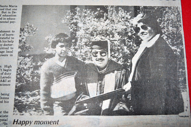 Julio F. Madrigal smiles with his diploma. To his left is his adolescent son and standing to this right is his wife.