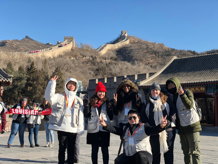 Melissa Olmeda taking a photo with locals in front of the Great Wall of China.