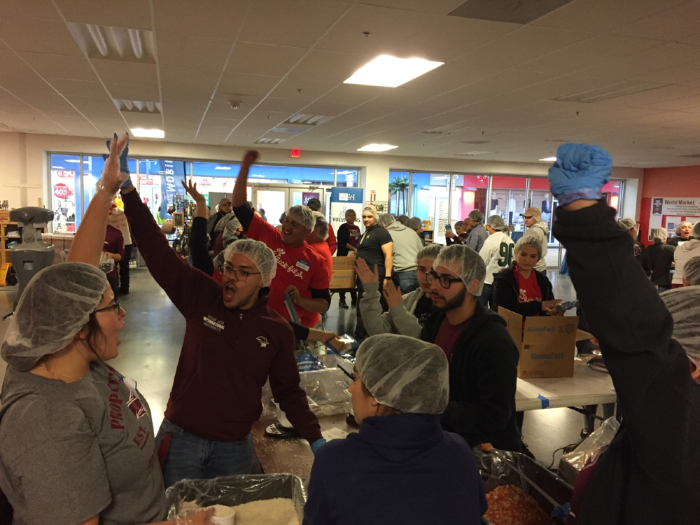 Students rallying up as they package meals during the annual TAMIU Make a Difference Day.