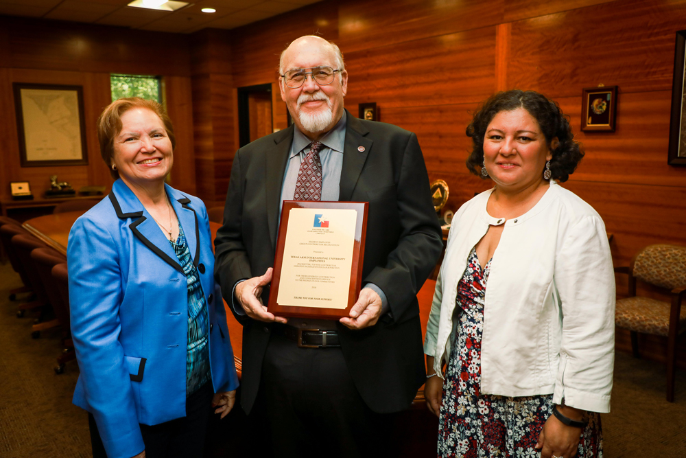 TAMIU SECC Committee members Mary Treviño, director of Migrant Programs, and Dr. Marcela Uribe, learning resources coordinator, presented a plaque recognizing the distinction to TAMIU president Dr. Pablo Arenaz.
