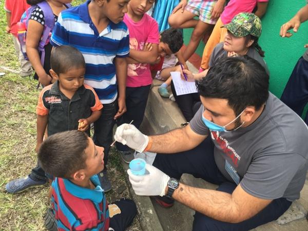 TAMIU Global Medical Brigade student conducting mouth swap for Honduran boy.