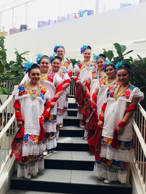 Folklorico dancers posing on a staircase.