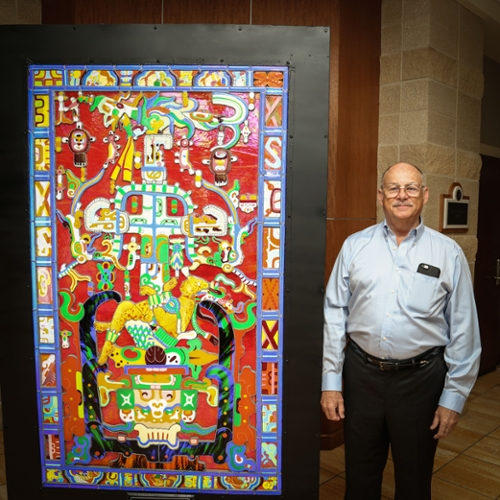 Artist Evan Quiros is pictured with his stunning Pakal Stained Glass Window, at home in the CFPA.